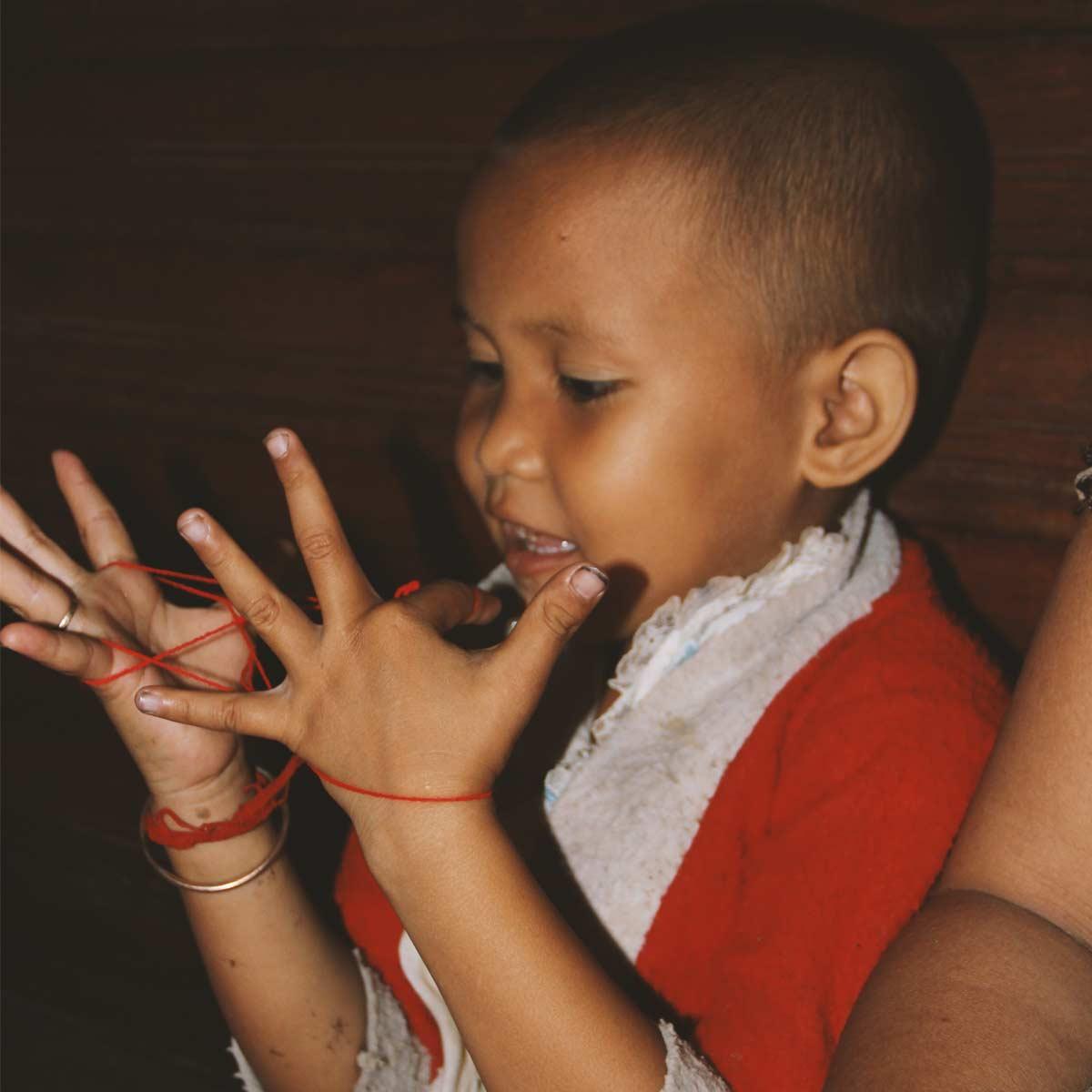 Kambodschanisches Kleinkind mit Fadespiel