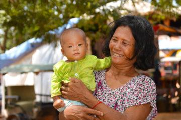 Stolz hält die Großmutter ihren Enkel auf dem Arm
