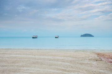 Blick auf das Meer mit zwei Fischerbooten und einer Insel am Otres Beach in Sihanoukville in Kambodscha