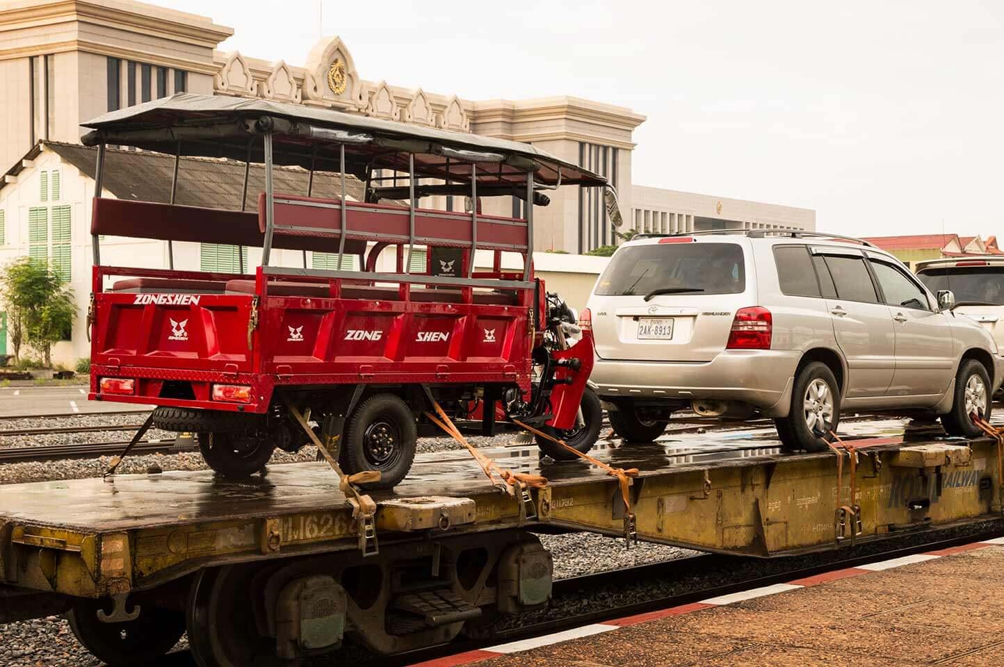 Tuk Tuk und Auto auf dem Zug am Bahnhof in Phnom Penh