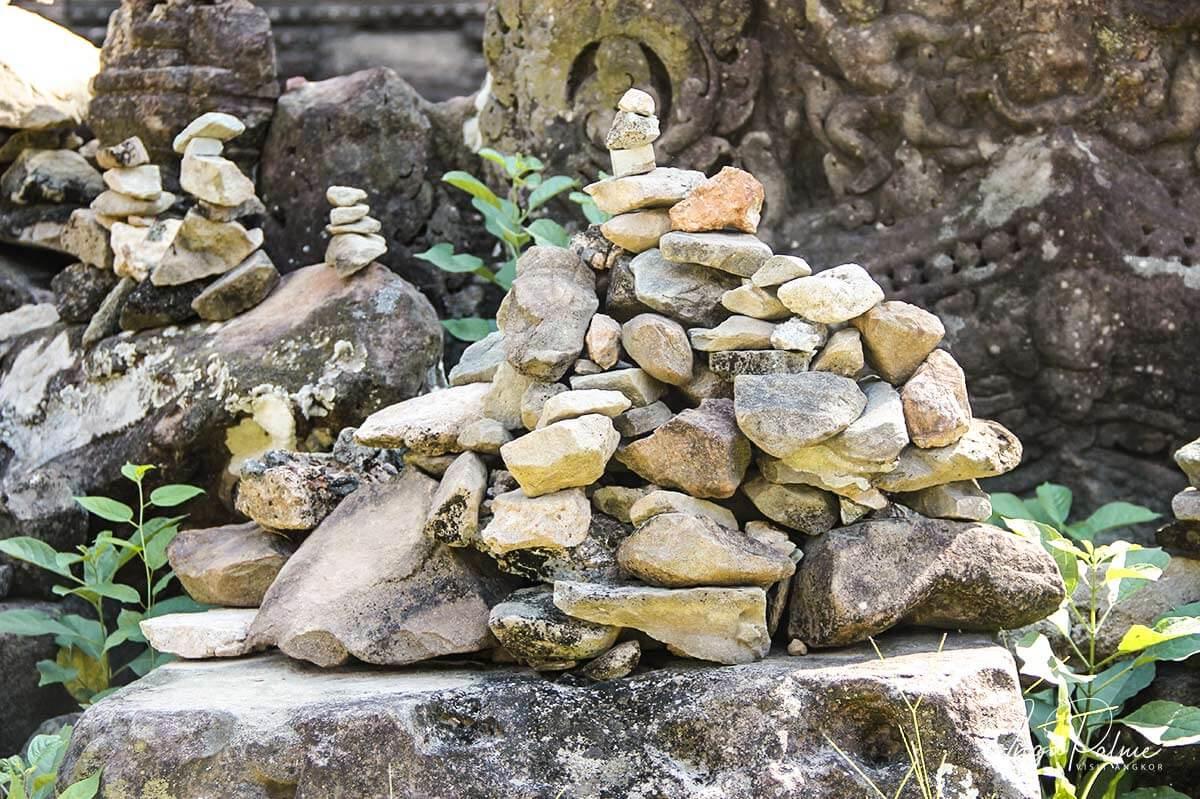Angkor Wat - Gläubige stapeln Steinchen übereinander