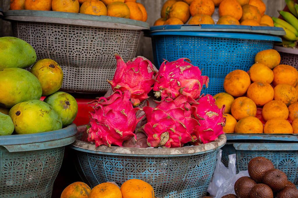 Pinke Drachenfrüchte, die in einem Korb auf einem Markt angeboten werden. Neben und über dem Korb sind weitere Körbe mit anderen Früchten.