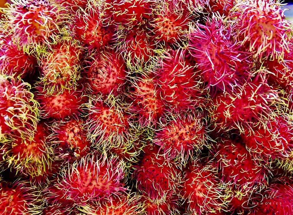 Rambutan, pinke Früchte, die übereinander liegen