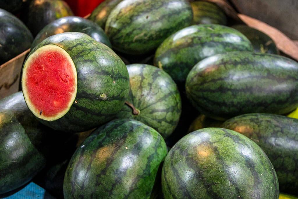 Wassermelonen, die übereinanderliegen. Eine Wassermelone ist aufgeschnitten und zeigt ihr rosarotes Fruchtfleisch.