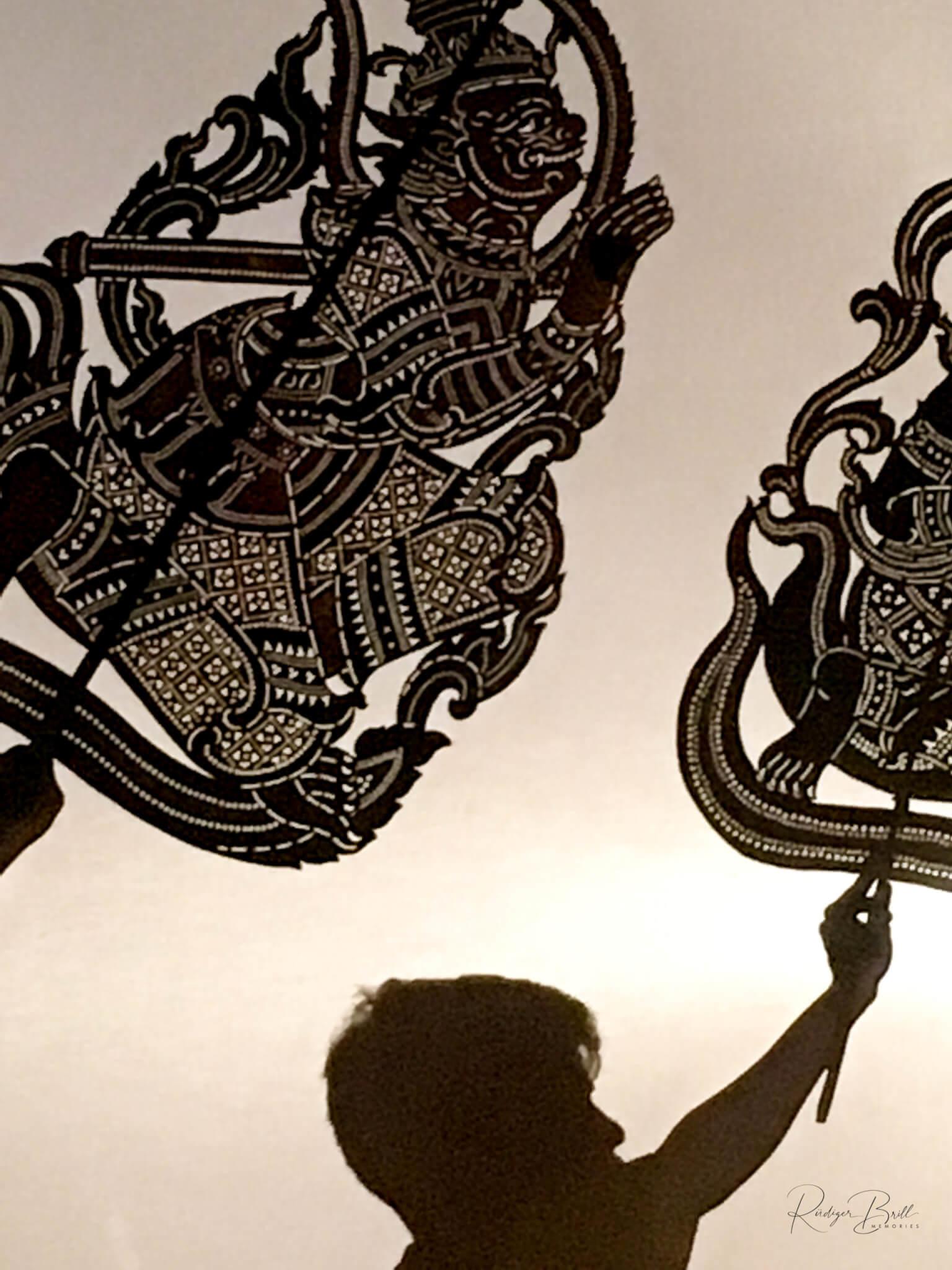Bildtafeln und Tänzer werfen ihre Schatten auf die Leinwand
