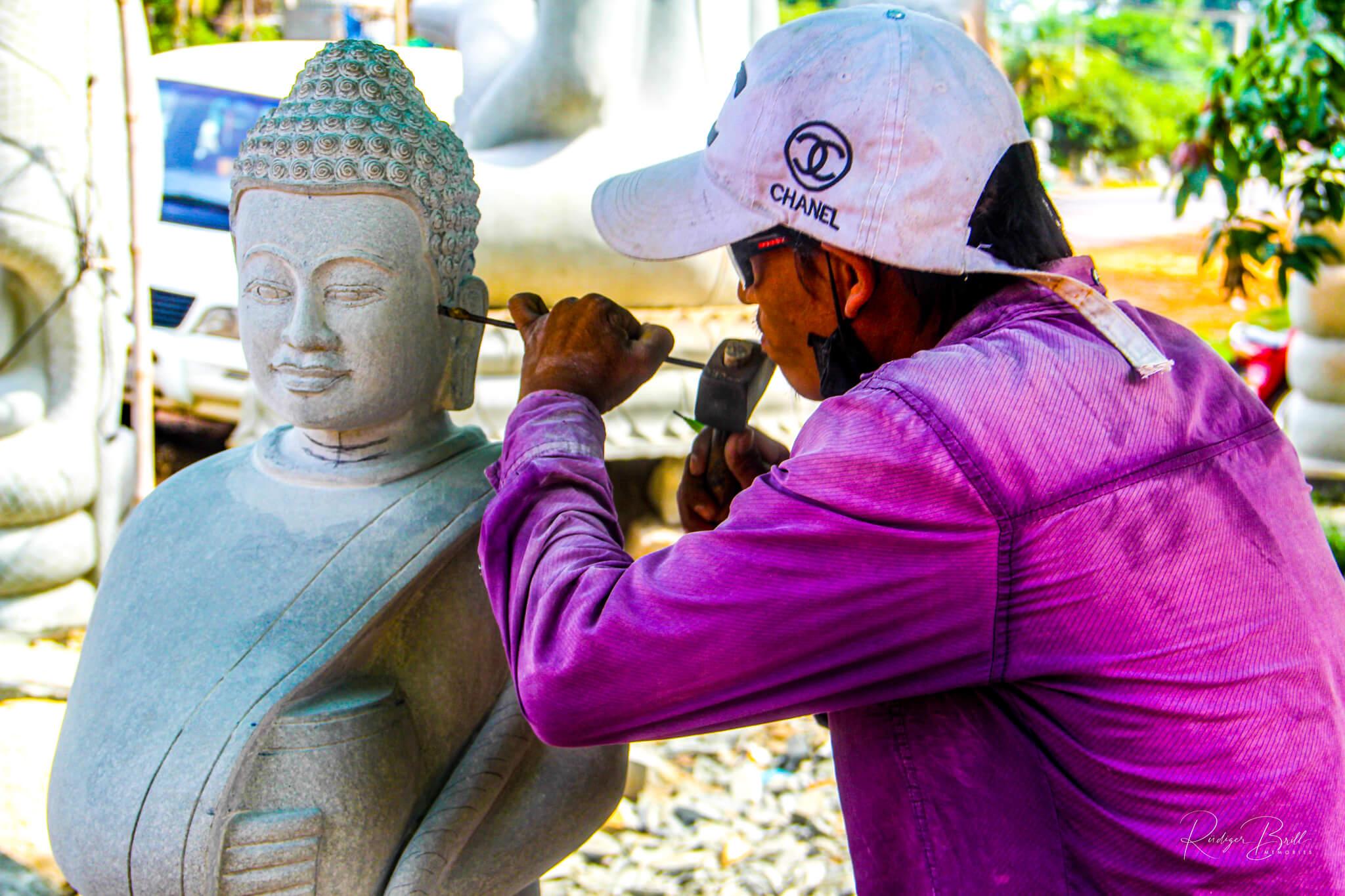 Ein Bildhauer in Kambodscha meißelt das Gesicht einer Buddha-Figur