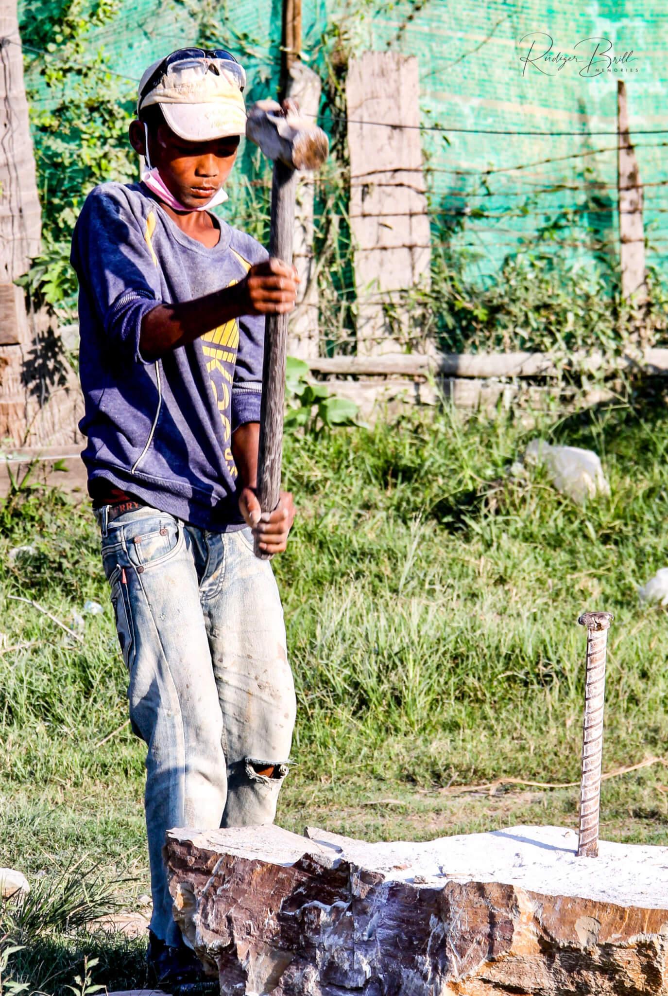 Ein Jugendlicher spaltet mit einem 8 Kilo schweren Hammer einen Steinblock