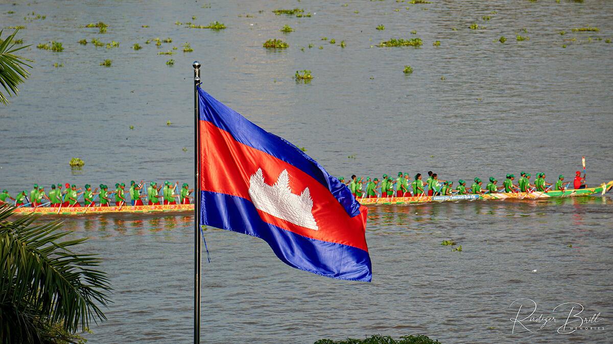 Ein Drachenboot mit 70 Ruderern in grüner Kleidung, das am Wettrennen bim Bon Om Touk, dem  Wasserfest in Phnom Penh, teilnimmt.