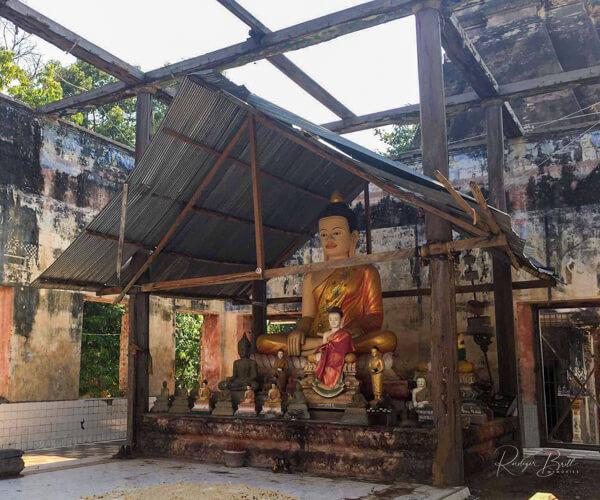 Eine Buddhastatue in einem zerstörten Tempel