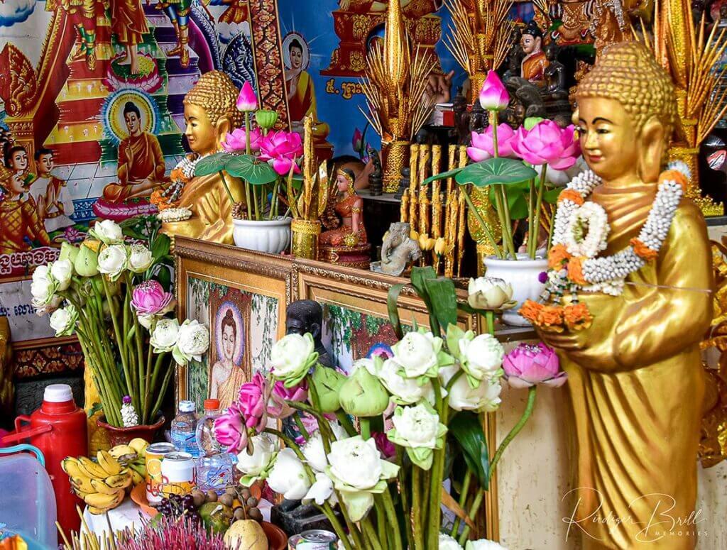 Mit vielen Lotosblumen geschmückte Buddhastatuen im Wat Steung Meanchey in Phnom Penh