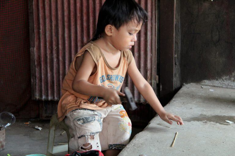 Cambodia: Child playing with a hammer