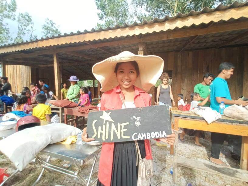 "Khmer young woman holding a sign with ""Shine Cambodia""."