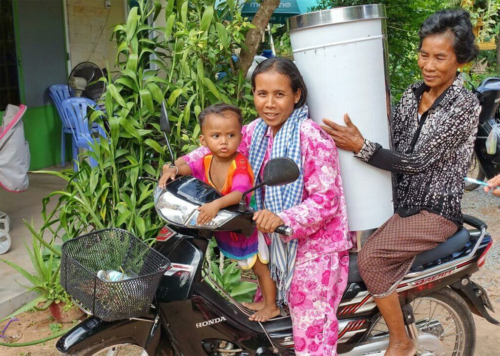"Happy Khmer family on a motorbike with a new Water Filter by charity ""Wasserzeichen"" from Germany"